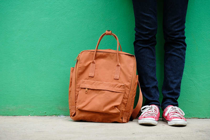 Student girl and school bag standing over green wall background with copy space, education, back to school concept
