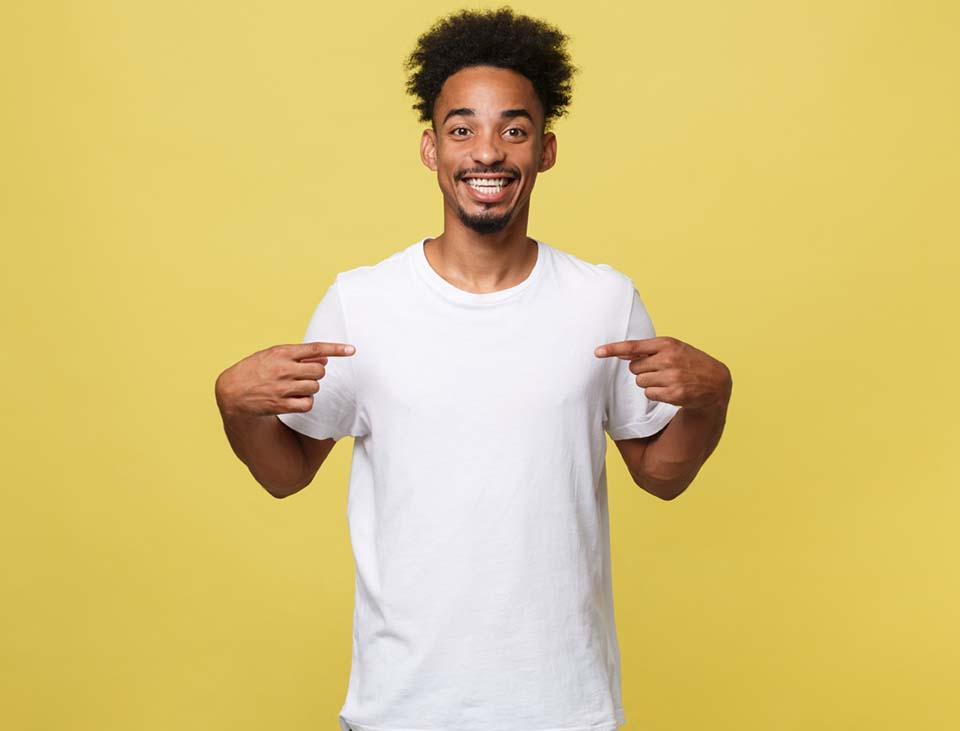 Portrait of handsome cheerful dark skinned male seller of clothes, dressed in casual white t shirt, indicates at blank copy space for your logo, isolated on yellow background. People, clothing, design.