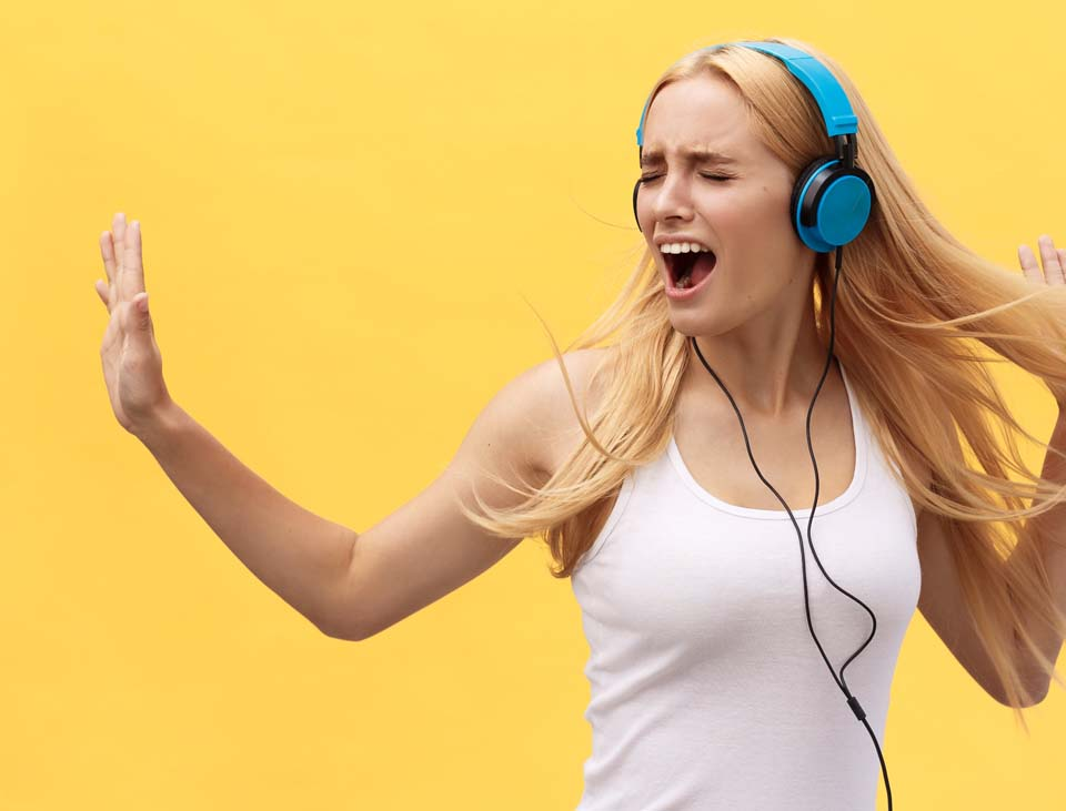 Lifestyle Concept: Portrait of a joyful woman in white t-shirt and listening to music with earphones while dancing and singing isolated over yellow background.